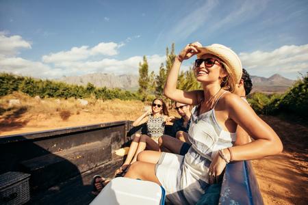 Ritratto di giovani amici felici che si siedono in un camioncino di partire per un viaggio su strada. I giovani che godono di un giro in strada di campagna.