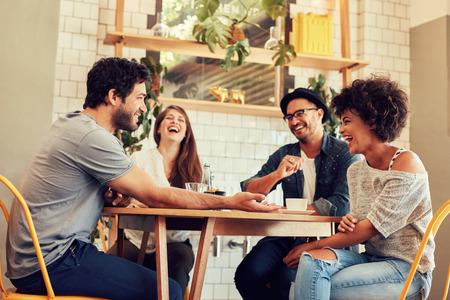 Mladí přátelé mají velký čas v restauraci. Skupina mladých lidí, kteří sedí v kavárně a usmívá se.