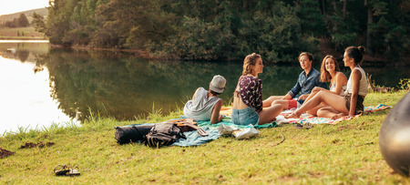 Young friends having picnic near a lake. Young friends enjoying a day at the lake.