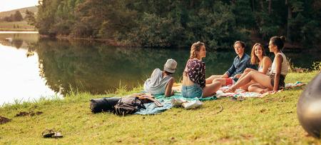 jezior: Młodzi przyjaciele posiadające piknik nad jeziorem. Młodzi przyjaciele korzystających dzień na jeziorze.