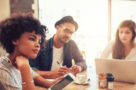 personas pensando: Cerca de retrato de joven mujer africana con la tableta digital y la gente en fondo en una mesa de café. Los jóvenes que se sientan en un restaurante con el ordenador portátil y la tableta digital.