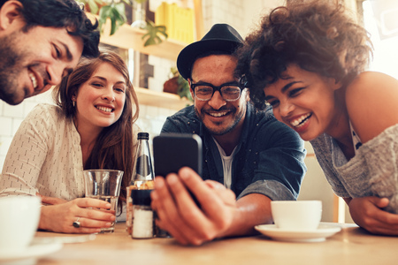 Group of friends sitting together in a cafe looking at mobile phone and smiling. Young guy showing something to his friends on his smart phone. Stock Photo