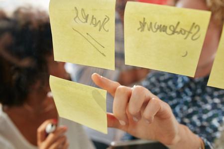 Hand van zaken vrouw wijzend op een notitie op een glazen wand tijdens het staan met collega's in het kantoor. Focus op vrouwelijke vinger.
