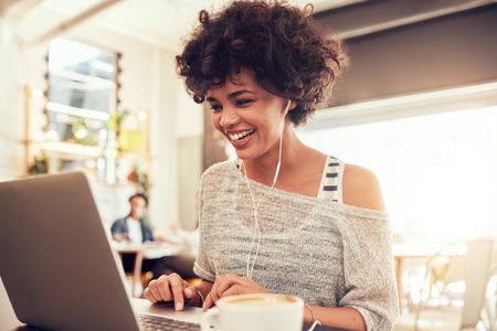 使用筆記本電腦幸福的女人形象而坐在咖啡館。年輕的非洲裔婦女坐在一間咖啡廳和筆記本電腦。 版權商用圖片