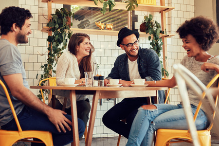 buddies: Young people having a great time in cafe. Friends smiling and sitting in a coffee shop, drinking coffee and enjoying together. Stock Photo