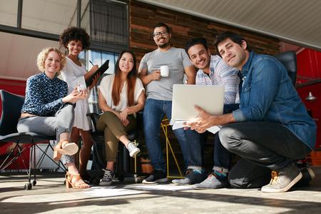 사무실에서 회의 창조적 인 전문가의 팀. 새 프로젝트를 위해 함께 작동하는 젊은 디자이너의 다민족 그룹.