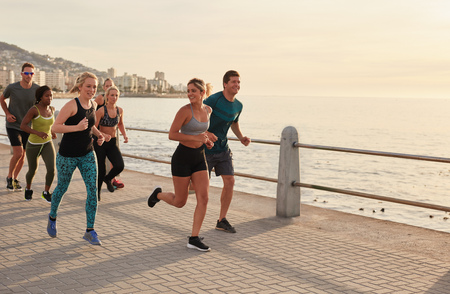 sports race: Young runners workout along a seaside promenade. Running club group training outdoors together by the sea.