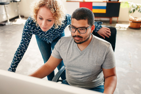 Portrait of two young graphic designers working on computer in office. Male and woman designers looking at computer monitor. photo