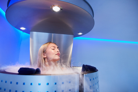 Portrait of young woman in a whole body cryo sauna. Female getting cryo therapy at the cosmetology clinic. Stock Photo