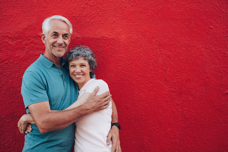 affectionate: Portrait of affectionate mature couple embracing against red background. Loving mature couple standing together with copy space.
