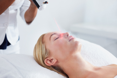 toxins: Localized cryotherapy session to the face of young caucasian woman. Ice cold nitrogen vapors applied to the facial skin, this eliminates inflammation, puffiness and flush out dirt and toxins from the skin.