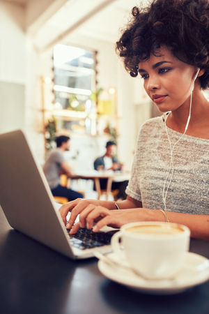surf shop: Portrait of attractive young woman with earphones working on laptop at a cafe. African female at a coffee shop surfing internet on laptop. Stock Photo