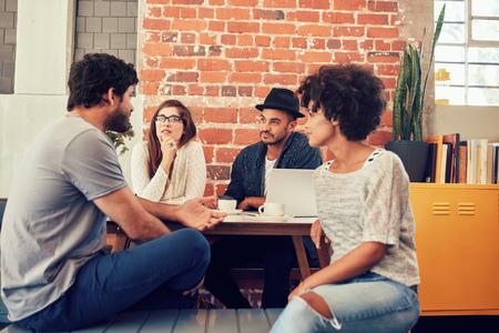 Groupe de jeunes amis assis et parler dans un café. Les jeunes hommes et femmes réunis à un café et discuter.