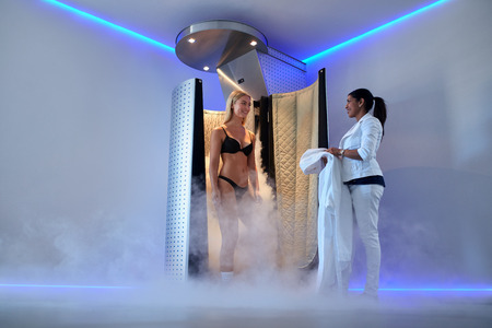 Full length portrait of young caucasian woman standing in a cryosauna, whole body cryotherapy.