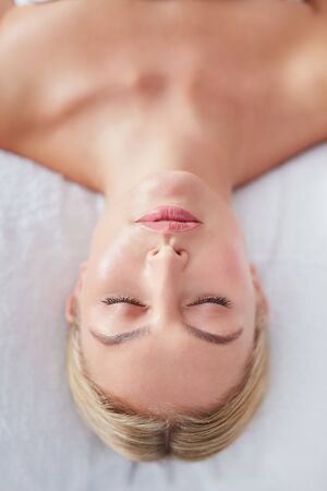 dayspa: Top view shot of beautiful young caucasian woman lying with her eyes closed on a massage table at dayspa