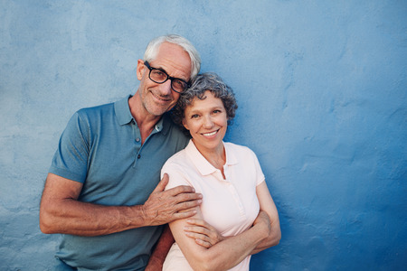 人像微笑成熟的情侶對藍色背景站在一起的。快樂的中年男人和女人靠在牆上。