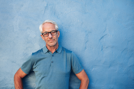 Portrait of a mature man standing against a blue background with copy space. Caucasian man wearing glasses leaning to a wall and staring at camera.