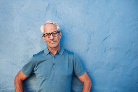 Ritratto di un uomo maturo in piedi contro uno sfondo blu con spazio di copia. Uomo caucasico che indossa occhiali appoggiato a un muro e fissando la fotocamera. Archivio Fotografico