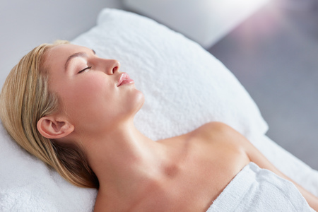 massage table: Close up shot of beautiful young blonde relaxing on massage table at spa. She lying with her eyes closed waiting for the spa treatment. Stock Photo