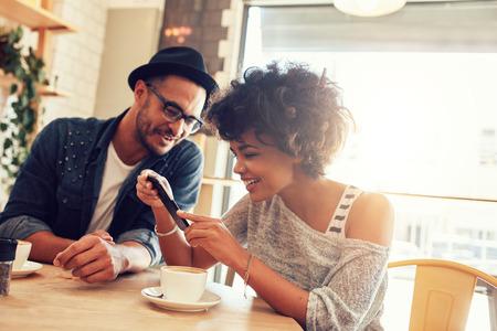 Portret van gelukkige jonge man en vrouw zitten samen in een restaurant en kijken naar een mobiele telefoon. Jonge vrienden kijken naar slimme telefoon tijdens het zitten in het cafe