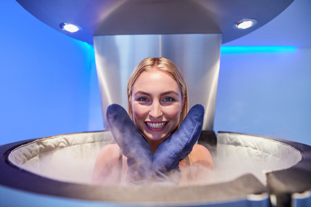 Portrait of a cute young woman in cryosauna booth for full body cryotherapy. Caucasian female in freezing chamber with nitrogen vapors.