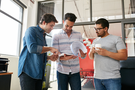 Creative people discussing plans in a standing meeting at modern office. Young male designer discussing new designs on paper with colleagues. photo