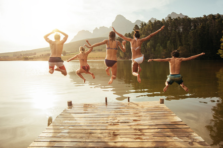 Ritratto di giovani amici che saltano dal pontile nel lago. Amici a mezz'aria su una giornata di sole al lago.