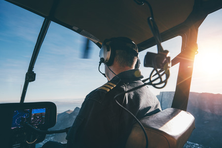 helicopter pilot: Rear view of a male wearing headphones flying a helicopter. Pilot flying an aircraft on a sunny day.