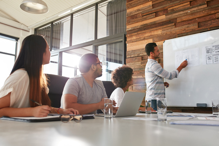 Disparo de un trabajador de oficina masculino que da la presentación creativa de sus colegas. Negocios que explica el plan de negocio para los compañeros de trabajo en la sala de conferencias. Foto de archivo