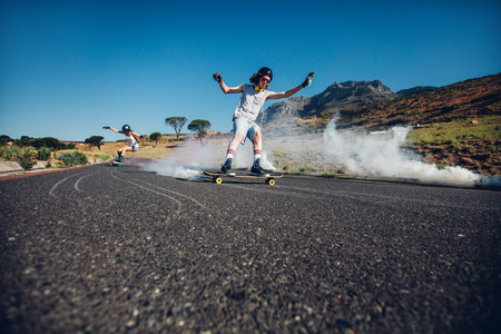 Outdoor shot of young people skating down the street. Man and woman practicing skating. Long board with smoke grenade. Stock Photo
