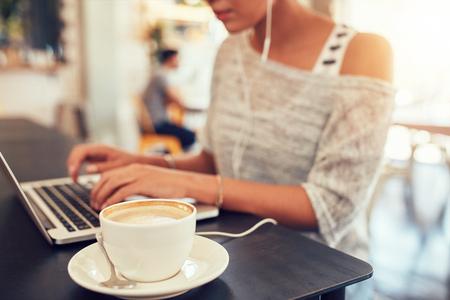 Close-up shot van een kopje koffie op een cafe tafel met een vrouw die op een laptop werkt.