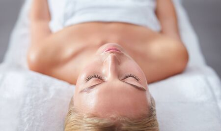 dayspa: Close up shot of young woman face relaxing on massage table. Female with her eyes closed at dayspa.