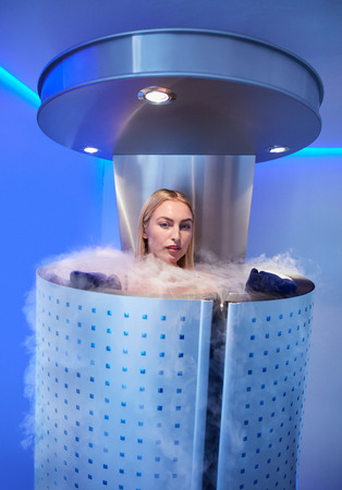 Portrait of beautiful young woman in a full body cryotherapy camber at cosmetology clinic. She is undergoing skin treatment using cold nitrogen vapors.
