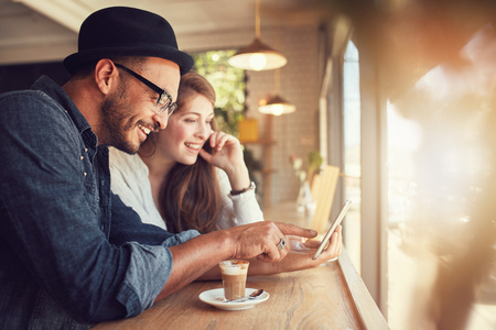 Smiling young couple in a coffee shop using touch screen computer. Young man and woman in a restaurant looking at digital tablet. Stock Photo