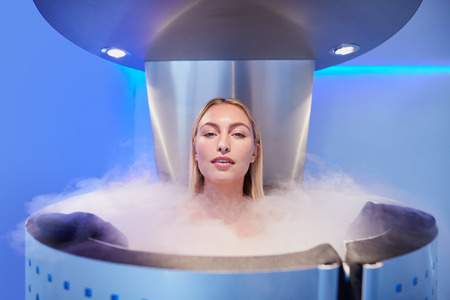 Portrait of a beautiful young woman in cryosauna cabin for whole body cryotherapy. Caucasian female in freezing chamber with nitrogen vapors. Banque d'images