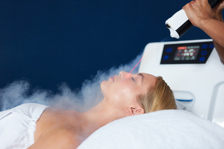 Beautiful young woman getting local cryotherapy therapy in cosmetology clinic. Beautician applying cold nitrogen vapors to the face of woman.