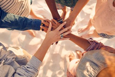 Close-up beeld van de handen van jonge mensen met een op stapel. Groep van gemengd ras vrienden op het strand met hun handen gestapeld. Stockfoto