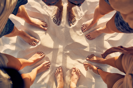 Top view image of feet of young people standing in a circle. Mixed race friends standing barefoot on sandy beach. Concept of unity in diversity. Stockfoto