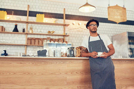 Portrait of young man working at a restaurant wearing an apron and hat leaning to the bar counter. Cafe owner standing at counter with a cup of coffee and looking away. Reklamní fotografie