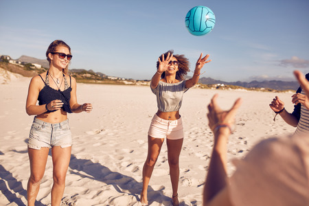 Portrait of young woman playing volleyball with friends on the beach. Group of friends playing volleyball.