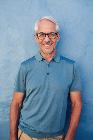 Portrait of handsome mature man with glasses looking at camera and smiling, he is leaning to against a blue wall. Stock Photo