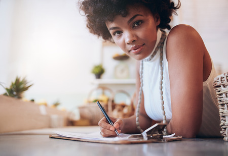 woman shop: Portrait of beautiful young african woman working in a juice bar. Female standing behind the counter and writing notes.