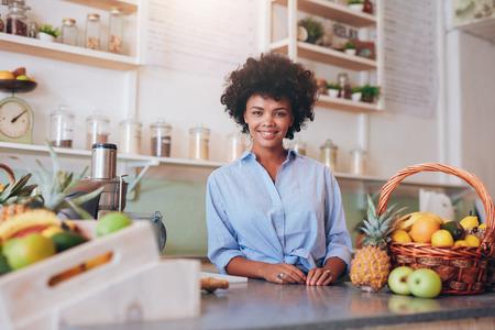 Ritratto di bella giovane donna che sta al contatore nella barra di succo che sorride alla macchina fotografica. Proprietario femminile africano della barra di succo. Archivio Fotografico