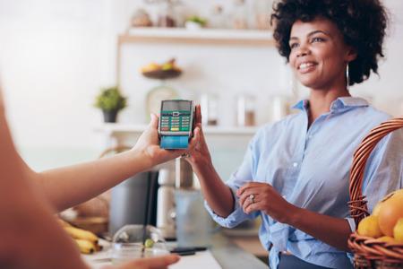 pagando: Recortar foto de una clienta pagar por su jugo con tarjeta de crédito en el bar de zumos. Centrarse en la mujer con las manos del lector de tarjetas de crédito.