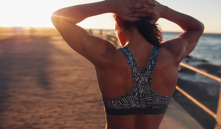 hand bra: Rear view shot of muscular woman in sports bra standing outdoors with her hands on her head at sunset.