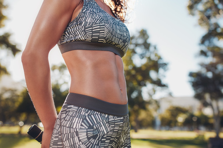 sixpack: Midsection shot of fit woman in sportswear outdoors at the park. Very fit body with strong six-pack abs.