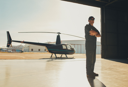 hangar: Full length portrait of confident pilot standing with his arms crossed in airplane hangar with a helicopter in background