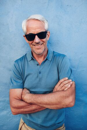 mature man: Portrait of happy mature man with sunglasses standing with his arms crossed against blue wall. Handsome mature male posing against a blue background.