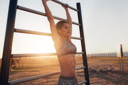 outdoor fitness: Portrait of young woman exercising on outdoor fitness equipments at sunset. Female exercising on wall bars outdoors.