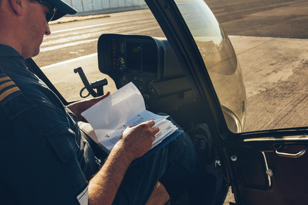 manuals: Male pilot sitting inside the helicopter and reading a manual book before the flight